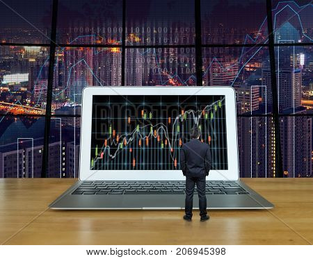 Businessman standing on the wood table which have the computer laptop showing the trading graph at the screen over the blurred photo of trading graph on cityscape background Business trading concept, 3D illustration