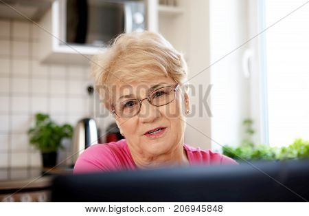 The senior woman surfing the internet with laptop computer, in home.