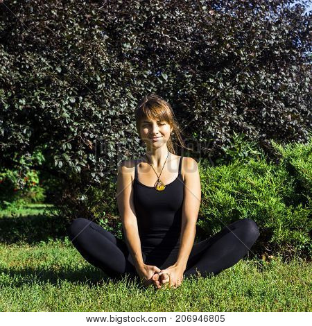 brown-haired girl doing yoga on the green lawn in the park