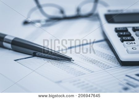 Accounting financial audit bank banking account stock spreadsheet data with glasses pen and calculator in washed blue monochrome financial concept for analysis, audit finance forensics