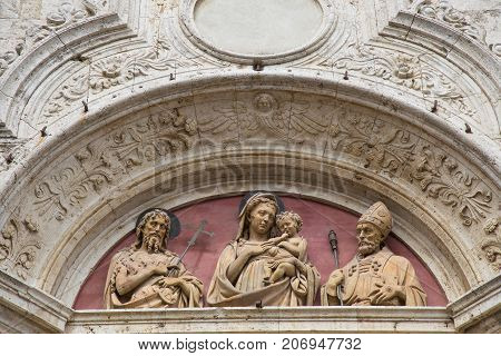 Depiction of three statues on the top of the door of a church in Montepulciano