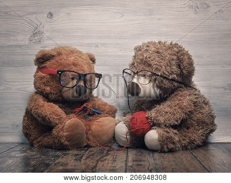Two Teddy bear. As old people - grandma knitting grandpa keeps a ball of yarn and helps the old lady. The concept of old age care tenderness