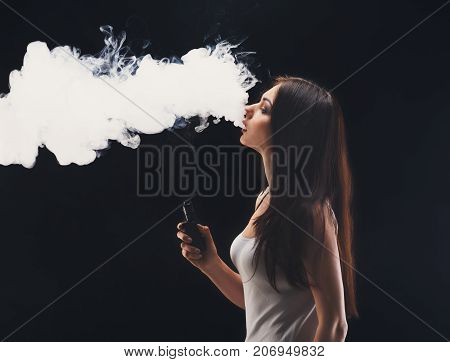 Young woman vaping, studio shot. Brunette girl blowing a cloud of smoke on black background. Nicotine free smoking and vapor concept, copy space