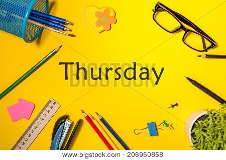 THURSDAY. Office supplies or student outfit on yellow table. Business creative consept, top view.