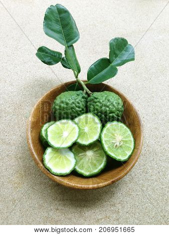 Kaffir Lime or Bergamot in wooden bowl on plywood background