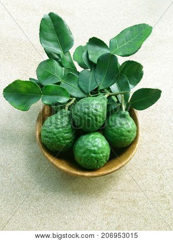 Kaffir Lime or Bergamot in wooden bowl on white background