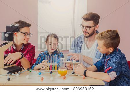 Stem education. Pupils with teacher doing biochemistry research in chemistry class, using laboratory tubes with colorful liquids