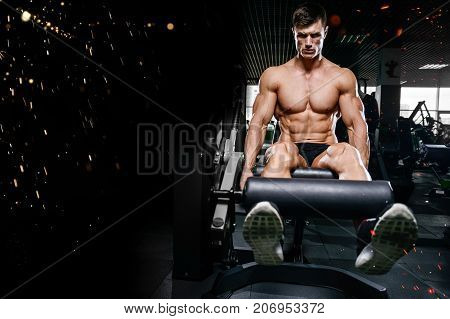 Handsome young muscular Caucasian man of model appearance working out in the gym training legs quadriceps and hamstrings on machines and with a barbell pumping up gaining weight and poses