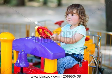 Toddler kid ride electric train attraction having fun at summer day lifestyle. Theme park for children vacation