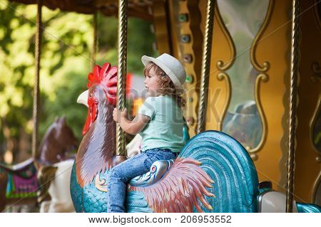 cute little girl at the theme park riding retro merry-go-round carousel