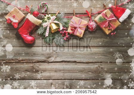 Festive background with Christmas presents, Santa Claus accessories and decoration on the clothesline in front of wooden board. Top view