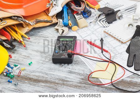 Set Of Construction Tools, Drawings And Multimeter, Wooden Background