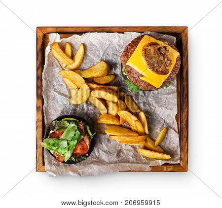 Take away burger menu on wooden tray isolated on white background. Black bun cheeseburger with baked potato wedges, fast food concept