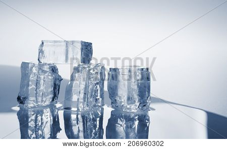 group of melted ice cubes with water puddle