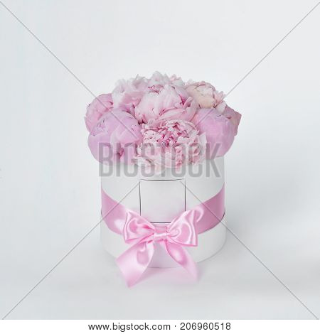 Luxury beautiful pink bouquet of peony flowers round white box with bow on gray background