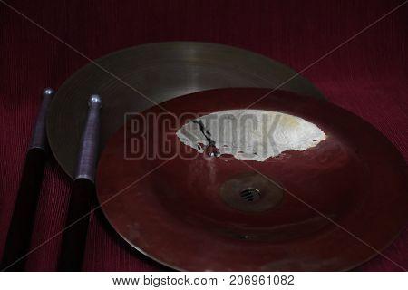 Cymbals piccoli a cupola con bacchette di metallo e legno con luce poco diffusa, scura