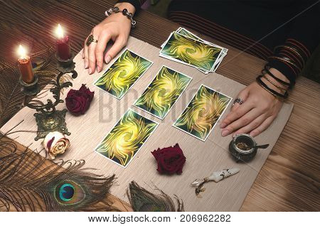 Fortune teller reading future by tarot cards on wooden table.