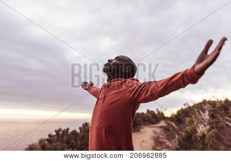 Young African man in a hoodie standing with his eyes closed and arms in the air embracing nature, while out for a run by the ocean