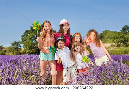 Happy preteen boys and girls playing with pinwheels in lavender field