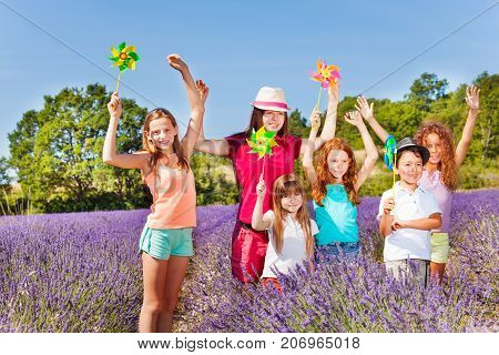 Group of happy preteen kids playing with multicolor pinwheels in lavender field at sunny day