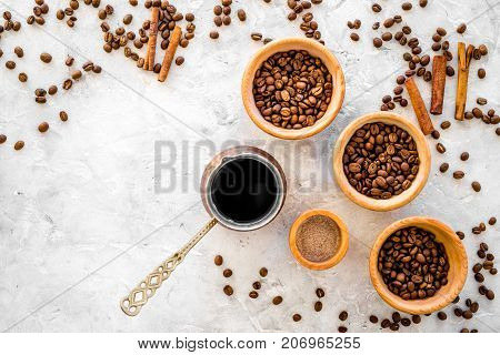 Make coffee in turkish coffee pot. Coffee beans, cinnamon on grey background top view.