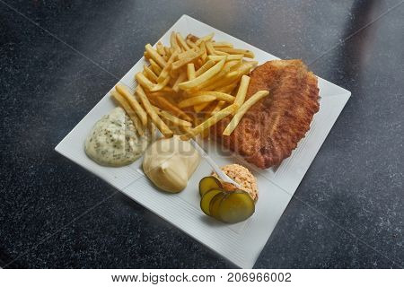 Fish and Chips served with sauces and salmon salad