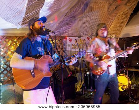 OAHU - FEBRUARY 20 2017: Rock Musicians Paul Izak and Tommy Osuna playing guitars at Optimysstique 2017 Campout under a giant sail at Camp Mokuleia on the North Shore of Oahu