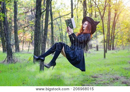 Levitation: The Witch Reads A Book Hanging Over The Ground, A Holiday Of Halloween.