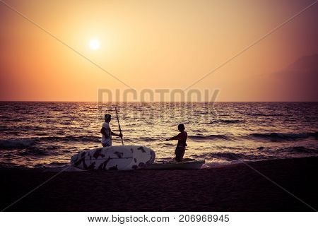 Two silhouttes of men in the sunset with surf boards at a sandy beach, Komos, Crete, Greece