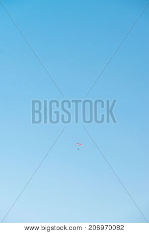 Paraglider in blue sky. Minimalistic style image