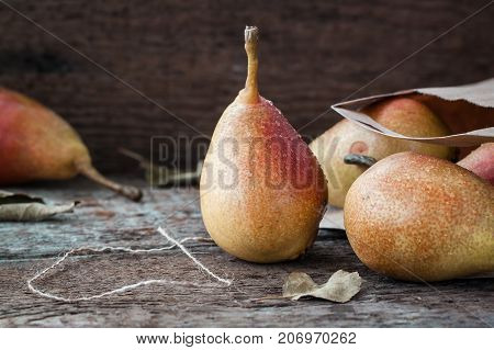 Red and yellow pears. Wooden background with the grocers bag