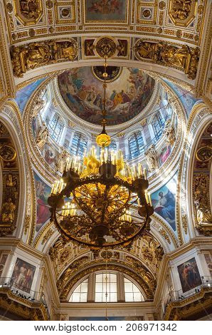 ST PETERSBURG RUSSIA - AUGUST 15 2017. Interior view of main dome and chandelier of St Isaac Cathedral in St Petersburg Russia