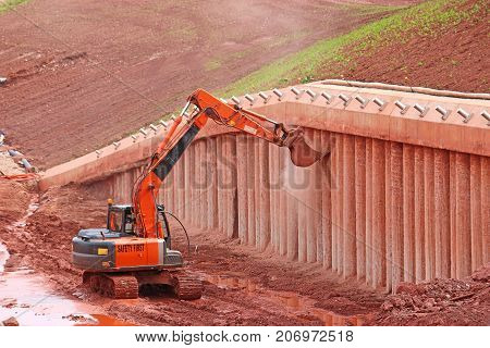 Digger scraping concrete bridge supports under construction