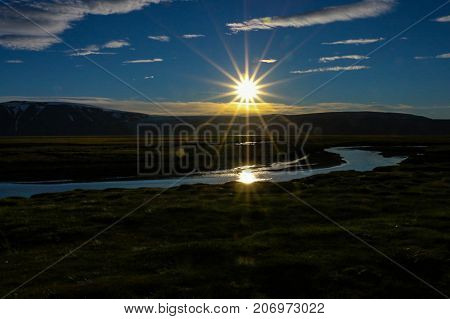 Midnight sun. A beautiful dreamy scenery of the midnight sun over the glacier Langjokull in the highland of Iceland, mystic reflection in the river Tjarna.