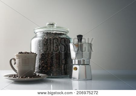An italian moka pot a small coffee machine presented along with a cup for coffee and a bowl of roasted coffee beans