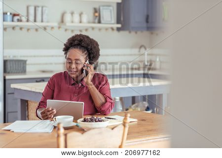 Smiling young African woman using a digital tablet and talking on a cellphone while sitting at a table working from home