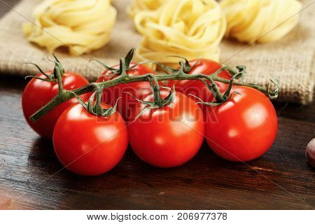 cherry tomatoes on a branch and raw tagliatelle paste in the background on a wooden background