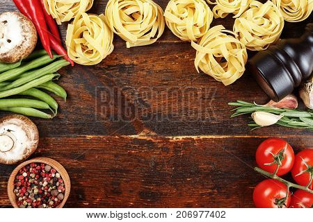 raw tagliatelle with tomatoes asparagus beans mushrooms on a wooden background space for text