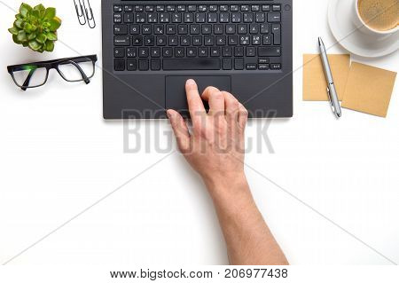 Overhead view of businessman touching touchpad on laptop at white desk in office