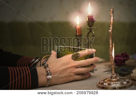 Tarot cards in fortune teller hands. Woman mixes tarot cards on wooden desk table. Reading future.
