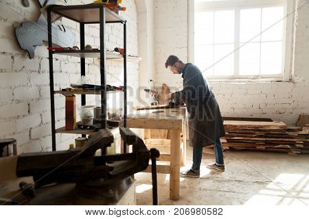 Side view of professional young joiner woodworking in planing shop garage. Skilled craftsman working on customized furniture, using sander. Carpentry services for construction, renovation and repair poster