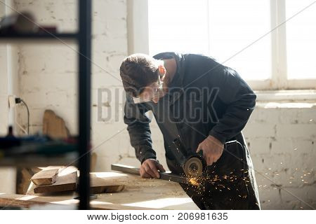 Tradesman in protective clothes using angle grinder to cut metal profile in workshop. Young man find part-time, side or short-term job in local carpentry. Craftsman makes own successful small business