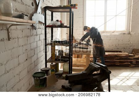 Skilled cabinet maker working with angle grinder in small workshop interior with instruments and tools on shelves, timber boards on floor. Small local business producing custom-made wooden furniture