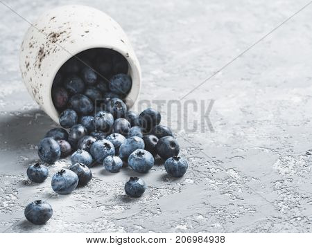 Blueberries on gray concrete background. Blueberry border design. Fresh picked bilberries scattered close up. Copyspace. Closeup