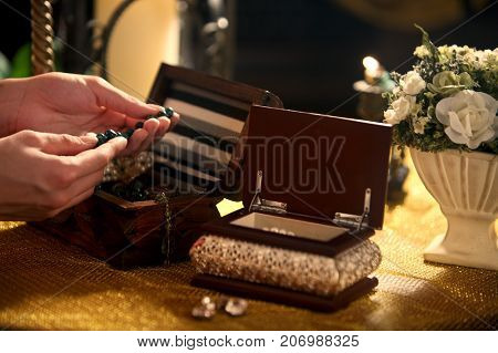 Jewellery box with female hands touch gems decorations. Candlelight background. Choice of jewelry for the first date.