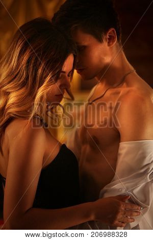 Couple dancing and kissing indoor. Romantic evening interior for loving couple. Loving people undress in intim interior. A lot of pictures in room. Wedding night.