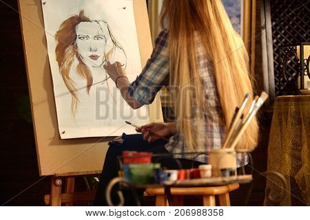 Artist painting on easel in studio. Girl paints portrait of woman with brush. Female painter seen from behind. Indoor home interior for handmade crafts. Student works as an artist.