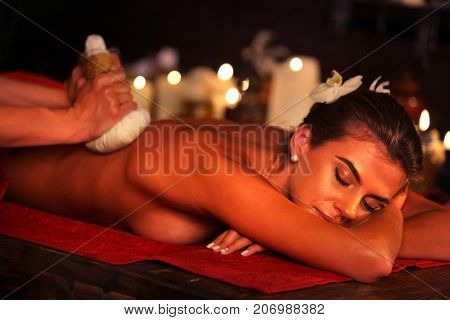 Spa gifts of woman massage in spa salon. Rest in elite beauty salon. Luxary interior in oriental therapy salon. Close up of female massage hands give herbs hot ball therapy. Group candels background.