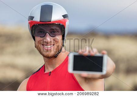 Phone sport app triathlon man biking road bike- triathlete using smartphone maps apps during cycling. Fit male cyclist on professional triathlon bicycle using mobile phone application