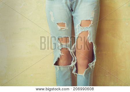 Women knees in jeans close to the studio holes in jeans fashion clothing. Hips and knees in fashionable jeans. Girl in jeans advertising